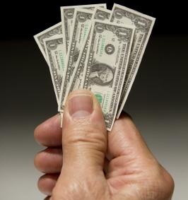 Man holding tiny dollar bills